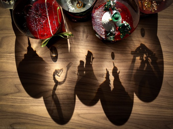 Shadows cast through holiday snow globes create a darker side of Christmas.